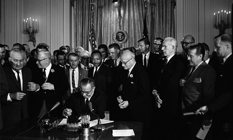 President Lyndon B. Johnson signs the Civil Rights Act into law