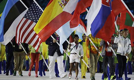 Simone Biles carrying the U.S. flag