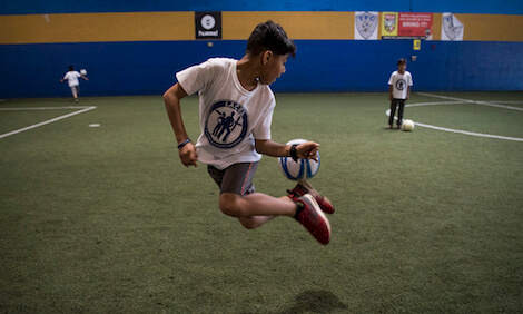 A boy from Afghanistan practices a soccer trick at soccer camp.