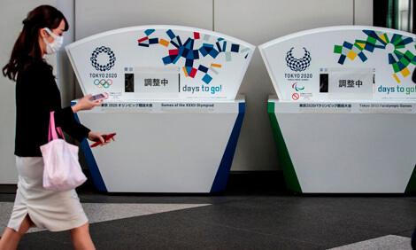 A woman wearing a face mask walks past a notice that states the Olympics have been postponed.